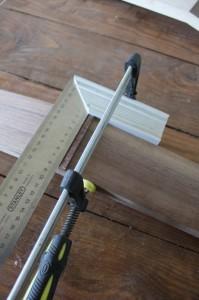 Fixation d'une équerre au sommet de l'angle formé par la tête et le manche,