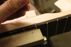 Dépose d'une goutte de super glue liquide au niveau du pied de frette de chaque côté